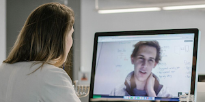 A young woman interviewing a male job applicant via video